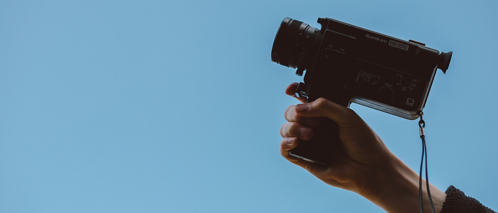 Hand holding a recording camera against a blue background
