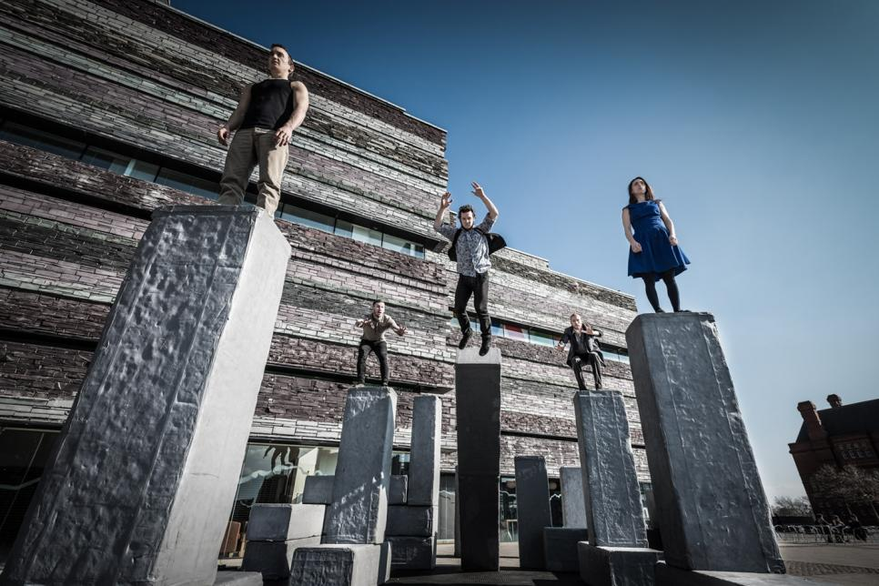 People stand on tall pillars as part of theatre performance.