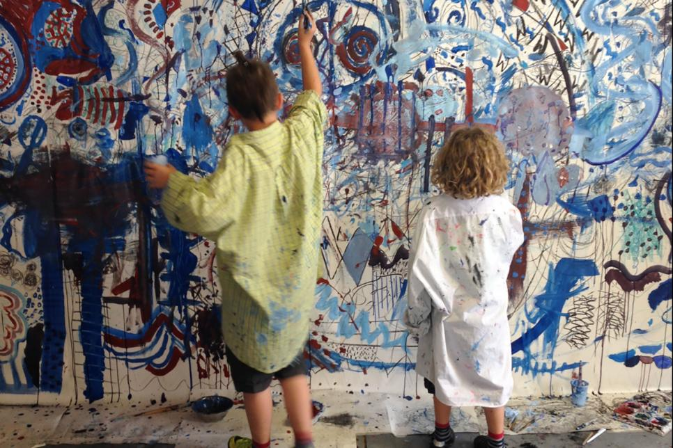 Two children painting a mural on a wall.