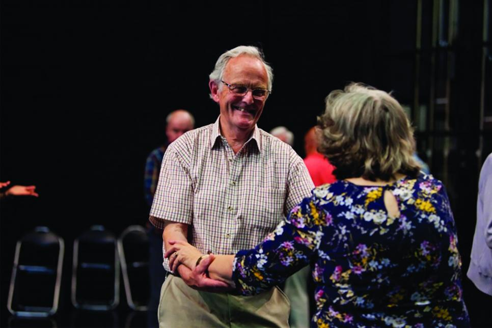Elderly man dancing with woman hand-in-hand