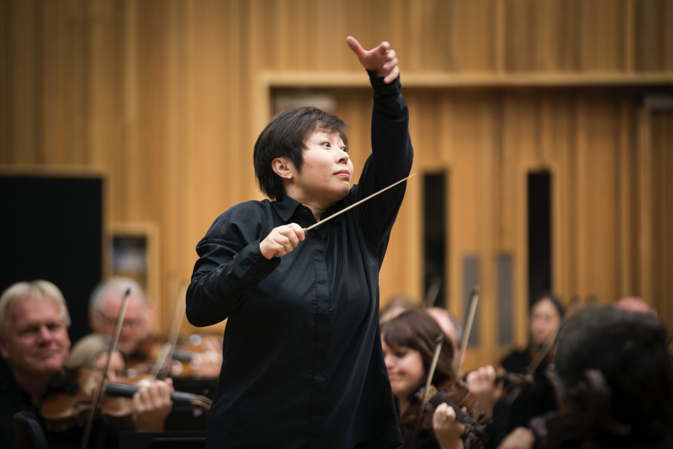 Closeup of the conductor Xian Zhang and BBC NOW orchestra