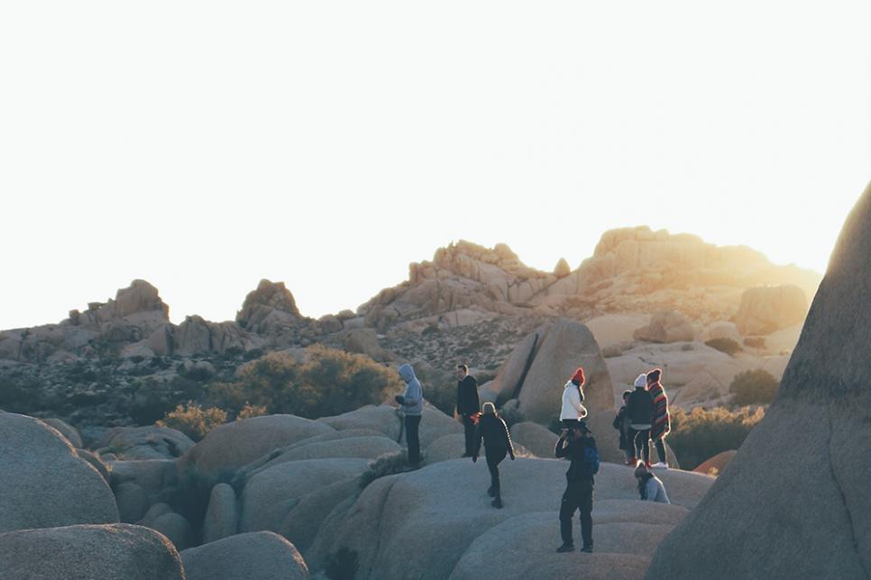 A group of people stand on big rocks outside as the sun sets