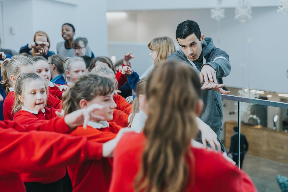 Man conducting a creative workshop with children in red jumpers
