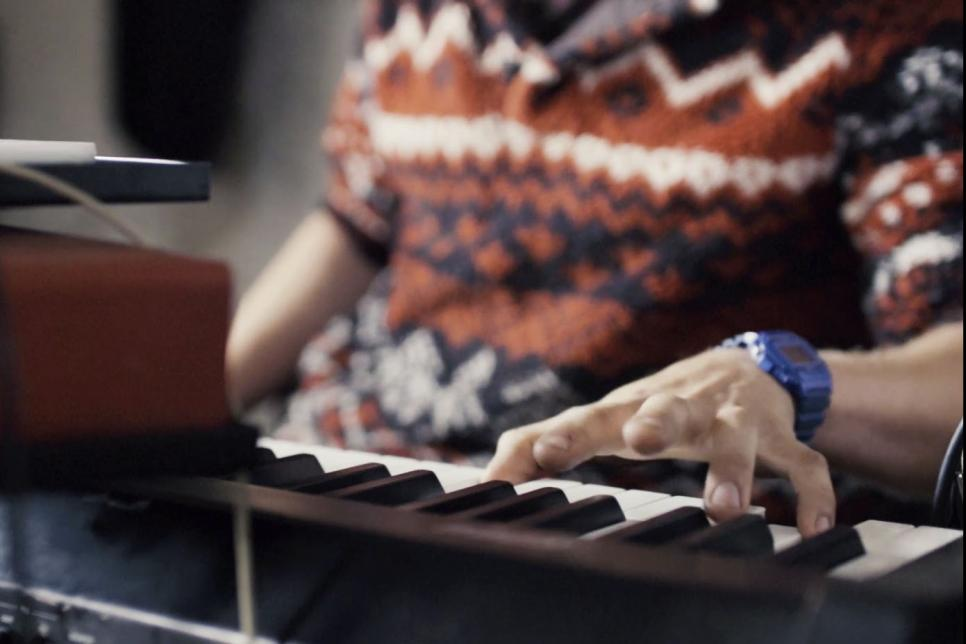Man in a colourful jumper playing the keyboard