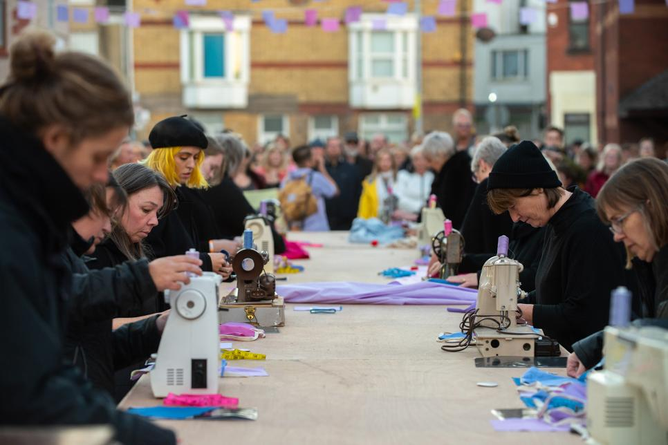 People at a long table sewing