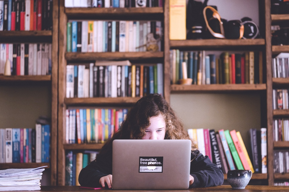 Young girl sits at a table looking at a laptop screen