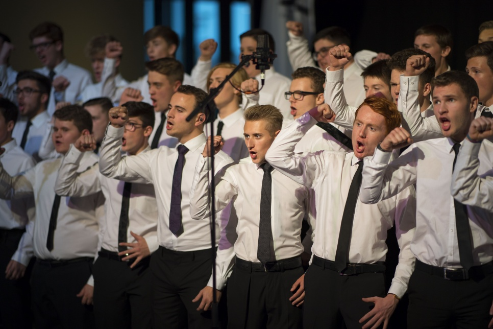 Only Boys Aloud Choir performing on stage with arms raised