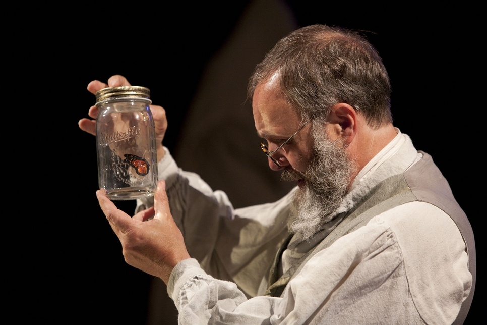 Man holds jar containing a butterfly