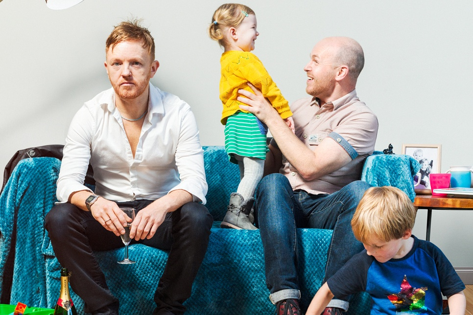 Two men and two small children on a sofa