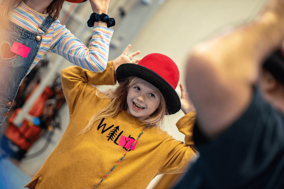 Photograph of young girl wearing hat smiles at camera
